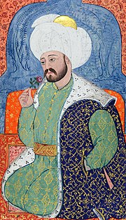 Persianate miniature showing a bearded man in rich robes and a large turban seated, and smelling a rose
