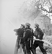 Members of the National Fire Service tackle a blaze in a house during a Civil Defence exercise in Fulham, London in 1942. D7908.jpg