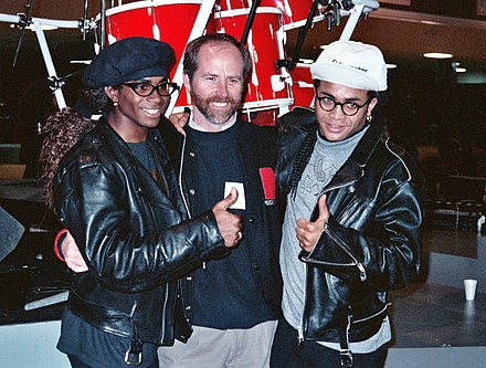 The Milli Vanilli duo pose with Michael Greene, chairman of NARAS, during the 1990 Grammys rehearsal. Milli Vanilli and C. Michael Greene.jpg