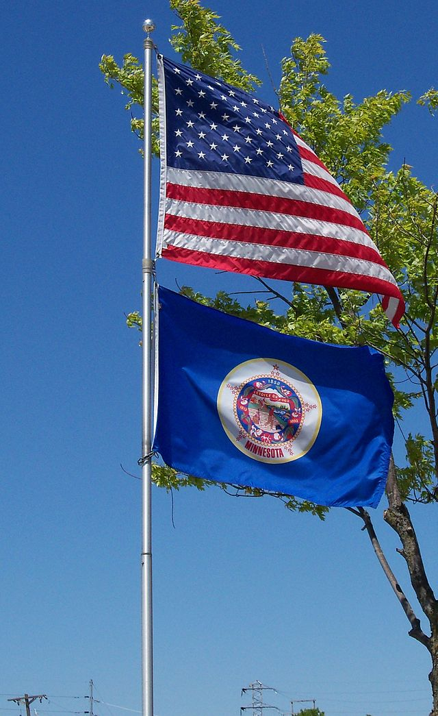 U.S. and Minnesota flags flying together. Minnesota state flag photo by AlexiusHoratius - Own work. Licensed under Creative Commons, via Wikipedia