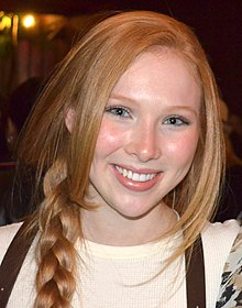 An eighteen year old redheaded caucasoid female is wearing a beige shirt with her ponytail draped over he right shoulder; she is smiling into the camera.