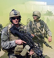 Michael Monsoor, a U.S. Navy SEAL, with a fellow SEAL team-mate, dressed in green camouflage uniform loaded with green combat uniforms. Both are carrying firearms and wearing sunglasses. There is a white-colored building and green smoke billowing in the background