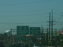 A four lane divided highway running through a business district with two overhead green signs. The left sign reads west Route 38 to Route 41 Ben Franklin Bridge Haddonfield 1/2 mile while the right sign reads Route 38 east Moorestown Mount Holly keep right