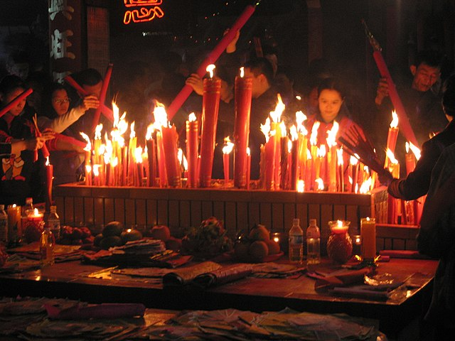 Chinese New Year eve in Meizhou at eastern Guangdong province, China. Fireworks are set off to ward off the bad spirits from the previous year and welcome the new year in. Candles and incense are also lighted during prayers, like this scene on Chinese New Year's Eve.