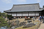 Wooden building with a large hip-and-gable roof and white walls.