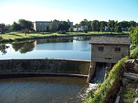 A body of water with a curved stone dam. At the right of the dam is a small stone house, underneath which water flows. There are buildings on land behind the dammed water
