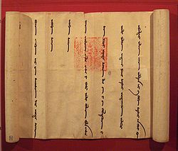 A partially unrolled scroll, opened from left to right to show a portion of the scroll with widely spaced vertical lines of a foreign language. Imprinted over two of the lines is an official-looking square red stamp with an intricate design.