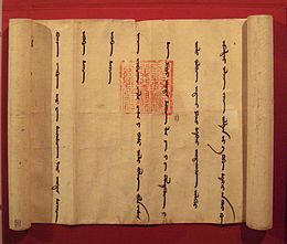 A partially unrolled scroll. opened from left to right to show a portion of the scroll with widely spaced vertical lines of cursive Mongol script. Imprinted over two of the lines is an official-looking square red stamp with an intricate design.