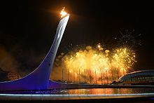 The tower with flame at the top. The background is sky with fireworks.