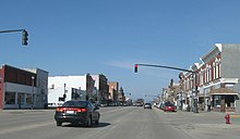 A car stopped at a traffic signal in the downtown area of a small town.