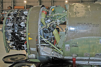 Republic P-47 Thunderbolt - A P-47 engine with the cowling removed. Uncompressed air enters through an intake under the engine and is carried to the turbosupercharger behind the pilot via the silver duct at the bottom. The olive-green pipe returns the compressed air to the engine
