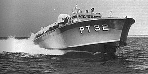 "a powerboat speeds across the water, riding high so the hull is exposed. ""PT 32"" is painted on the hull in large white letters."