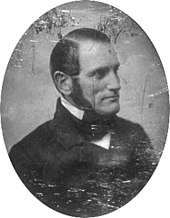 A black and white head-and-shoulders photographic portrait of Parkman. He faces to the right, sports long sideburns, and wears a dark suit and tie. The photograph has scratches and other damage.