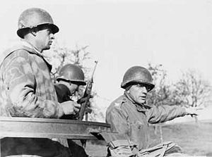 Three men in uniforms with steel helmets. One holds a rifle; another, wearing glasses, points to something in the distance.