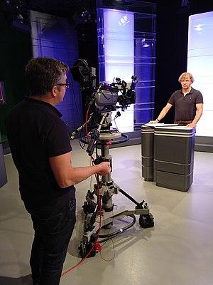 """Peter Tümmers von Schoenebeck steht vor einer Studion-Kamera in Daimlers AKUBIS-Studion in Stuttgart und zeichnet einen Impulsvortrag zum Thema """"Agile Führung"""" auf."""