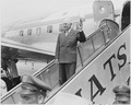 Photograph of President Truman waving from the steps of his airplane as he prepares to leave Washington to attend the... - NARA - 200390.tif