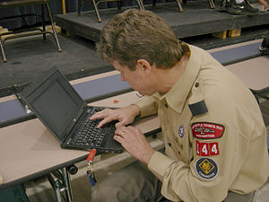 Cub Scout Master confers with his laptop durin...