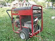 Portable generator side view showing gasoline engine.