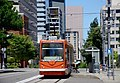 Portland Streetcar with passenger in wheelchair boarding - 5th & Montgomery (2015).jpg