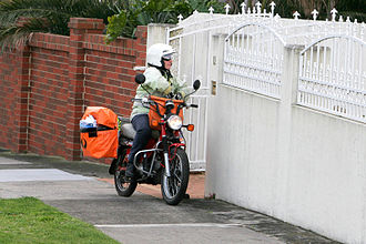 Mail carrier - An Australian postie riding a motorbike in Melbourne.