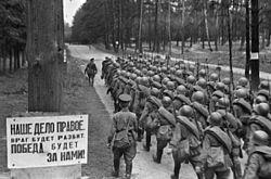 """Quân dự bị động viên của Liên Xô tiến ra mặt trận. Bảng trên cây bên trái ảnh có ghi dòng chữ: """"Chính nghĩa thuộc về chúng ta. Kẻ thủ sẽ bị tiêu diệt. Chiến thắng sẽ nằm trong tay chúng ta"""" (Ảnh của RIA NOVOSSTI)"""