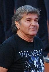 Un hombre que llevaba una camisa de color negro waliking en una pista de tenis, con otros personas detrás de él.