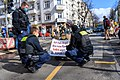 """Rebellion of One Rebel of Extinction Rebellion blocks a road, sign reads """"I am afraid that my children will suffer because of the climate crisis."""" (51007303855).jpg"""