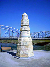 A stone obelisk indicating the level of past floods at different heights. In the background a bridge and a river can be seen.