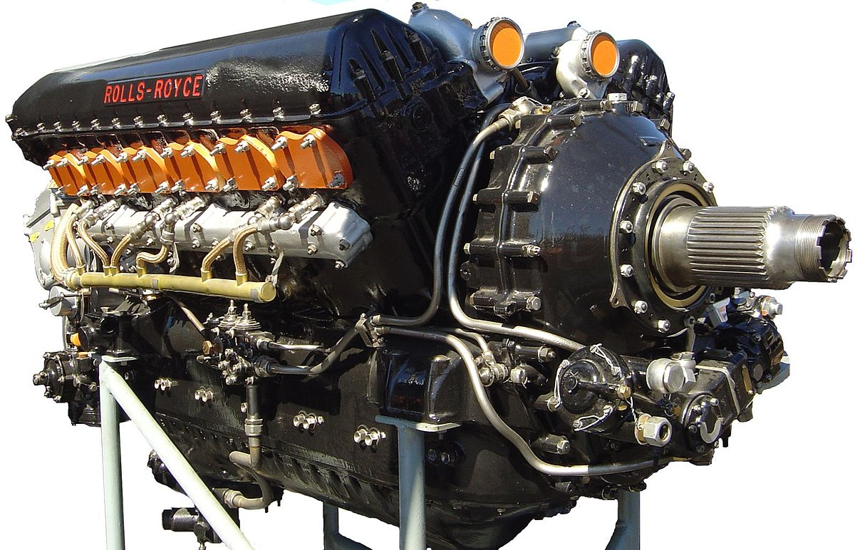 A front right view of a black-painted aircraft piston engine. The words 'Rolls-Royce' appear in red text on the camshaft cover.