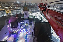 A rooftopper on a crane over the swiss national museum in winter at the time of the christmas event.