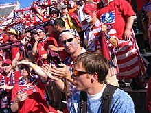 A number of American fans, dressed in red, stand in bleachers holding United States paraphernalia.