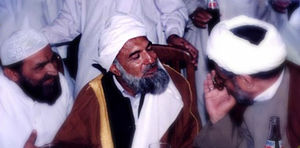 Riaz Ahmed Gohar Shahi - Shahi at an event at Imam Bargah-e-Noor-e-Iman Mosque, in Karachi, Pakistan. He is seen here speaking to two religious clerics from different sects within Islam: Shia Islam and Sunni Islam.