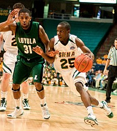 """A man in a white jersey with green """"SIENA"""" and """"25"""" on front dribbles a basketball past another man in a forest-green jersey with white """"LOYOLA"""" and """"31"""" on front."""