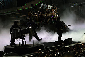 A rock band silhouetted on a dark stage with white fog on the stage floor