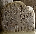 """Stela showing """"Isis the Great Goddess"""" sitting and holding a was-sceptre. A man, the head of necropolis workers, adores her. From Egypt, Middle Kingdom. The Petrie Museum of Egyptian Archaeology, London.jpg"""