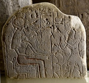"Was-sceptre - Stela showing ""Isis the Great Goddess"" sitting and holding a was-sceptre. A man, the head of necropolis workers, adores her. From Egypt, Middle Kingdom. The Petrie Museum of Egyptian Archaeology, London"
