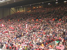 A stand which is full of people standing to support their team. There are a number of flags, scarfs, and banners in the crowd.