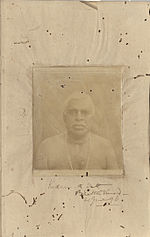 A faded sepia photograph of an old man with neck beads on a deteriorated paper page.