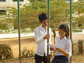 Teenage boy and girl, the girl is sitting on a swing reading, the boy standing next to her.jpg