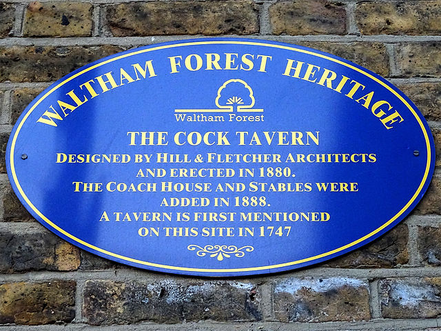 Blue plaque № 9668 - The Cock Tavern. Designed by Hill & Fletcher Architects and erected in 1880. The Coach house and stables were added in 1888. A tavern is first mentioned on this site in 1747