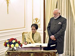 The State Counsellor of Myanmar, Aung San Suu Kyi signing the visitors' book, at Hyderabad House, in New Delhi on January 24, 2018. The Prime Minister, Shri Narendra Modi is also seen