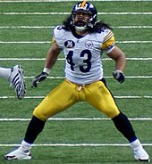 A man wearing white football jersey and yellow pants