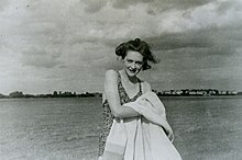 Photograph of a woman wearing a swimsuit, drying herself with a towel