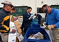 US Navy 040416-N-8921O-002 Sailors assigned to Patrol and Reconnaissance Wing Ten (PATWING 10) rummage through several trash cans to separate regular trash from recyclable material.jpg