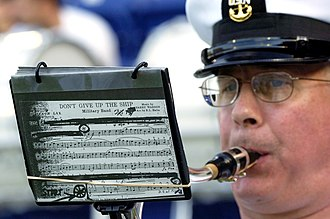 "United States Naval Academy Band - A United States Naval Academy Band musician plays a service song prior to the kick-off of a season home-opener football game, which pitted the Navy ""Midshipmen"" against Duke ""Blue Devils."""
