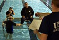 US Navy 051030-C-2023P-635 U.S. Coast Guard 3rd Class Alex Parrey receives instructions before being flipped upside-down as part of a water survival training course.jpg