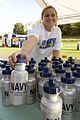 US Navy 060819-N-3390M-015 Hospitalman Karrie Cook Branch Medical Clinic, Naval Station Everett, organizes water bottles at the Navy booth prior to the start of the Aqua Sox baseball game.jpg