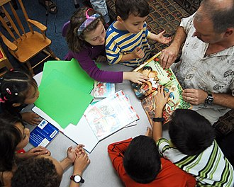 Vocabulary development - Children in school share an interactive reading experience.