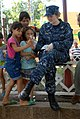 US Navy 090626-N-9318F-119 Lt. Michelle Mathis, embarked aboard the Military Sealift Command hospital ship USNS Comfort (T-AH 20), hands stickers out to local children during a Continuing Promise 2009 medical community service.jpg