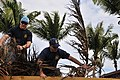 US Navy 100109-N-8433N-437 Chief Naval Air Crewman Tracy Moran and Naval Air Crewman 2nd Class Jeremy Gardner collect coconut tree fronds.jpg